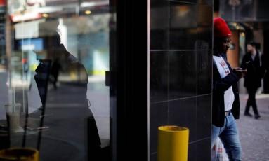 Em Boston, nos EUA, mulher usa laptop e homem, celular Foto: BRIAN SNYDER / REUTERS