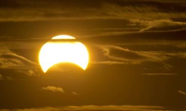 Um eclipse parcial do Sol, como o que será visível neste domingo em boa parte do Brasil neste domingo, visto entre nuvens pouco depois do amanhecer em Queens, Nova York, em novembro de 2013 Foto: AFP/STAN HONDA