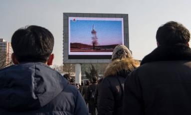 Norte-coreanos assistem a teste com míssil balístico em Pyongyang Foto: KIM WON-JIN / AFP