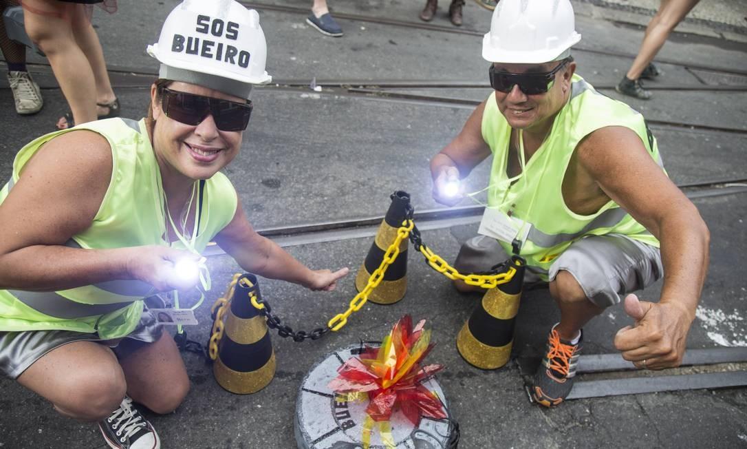 Com bom humor, dupla de foliões no Céu na Terra 'fiscaliza' bueiros para evitar acidentes no meio da festa Foto: Ana Branco / Agência O Globo