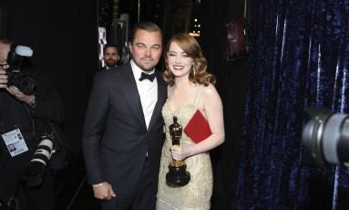 Emma Stone, ao lado de Leonardo DiCaprio, com o envelope de melhor atriz debaixo do braço Foto: Matt Sayles / AP