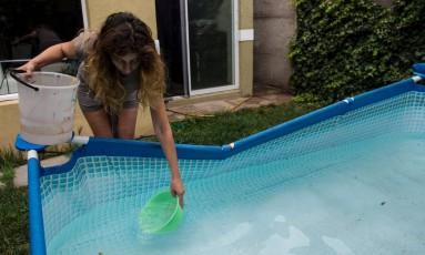 Mulher recorre à piscina de sua casa para conseguir água na capital do Chile Foto: AFP