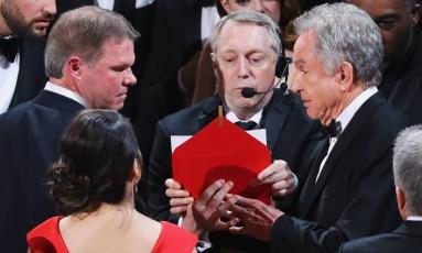 O momento em que auditores consultam o envelope para averiguar o erro. À direita, o veterano Warren Beatty Foto: LUCY NICHOLSON / REUTERS