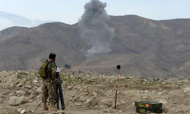 Soldado observa área atingida por bombardeamento aéreo pelo exército dos EUA em Nangarhar, no Afeganistão Foto: NOORULLAH SHIRZADA / AFP