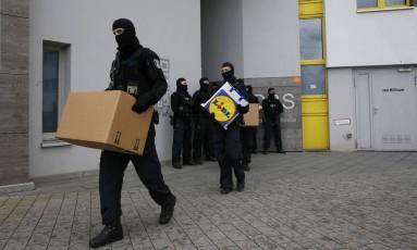 Policiais carregam caixas de um prédio na região de Maerkisches Viertel, em Berlim Foto: FABRIZIO BENSCH / REUTERS
