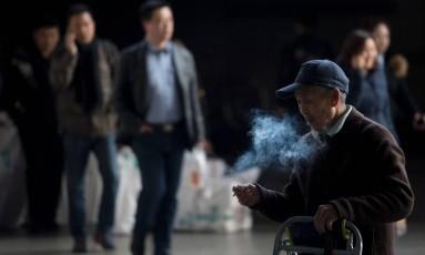 Homem fuma cigarro em estação de trem em Xangai Foto: JOHANNES EISELE / AFP