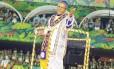 Monarco desfila como sacerdote do samba, num traje azul, branco e dourado