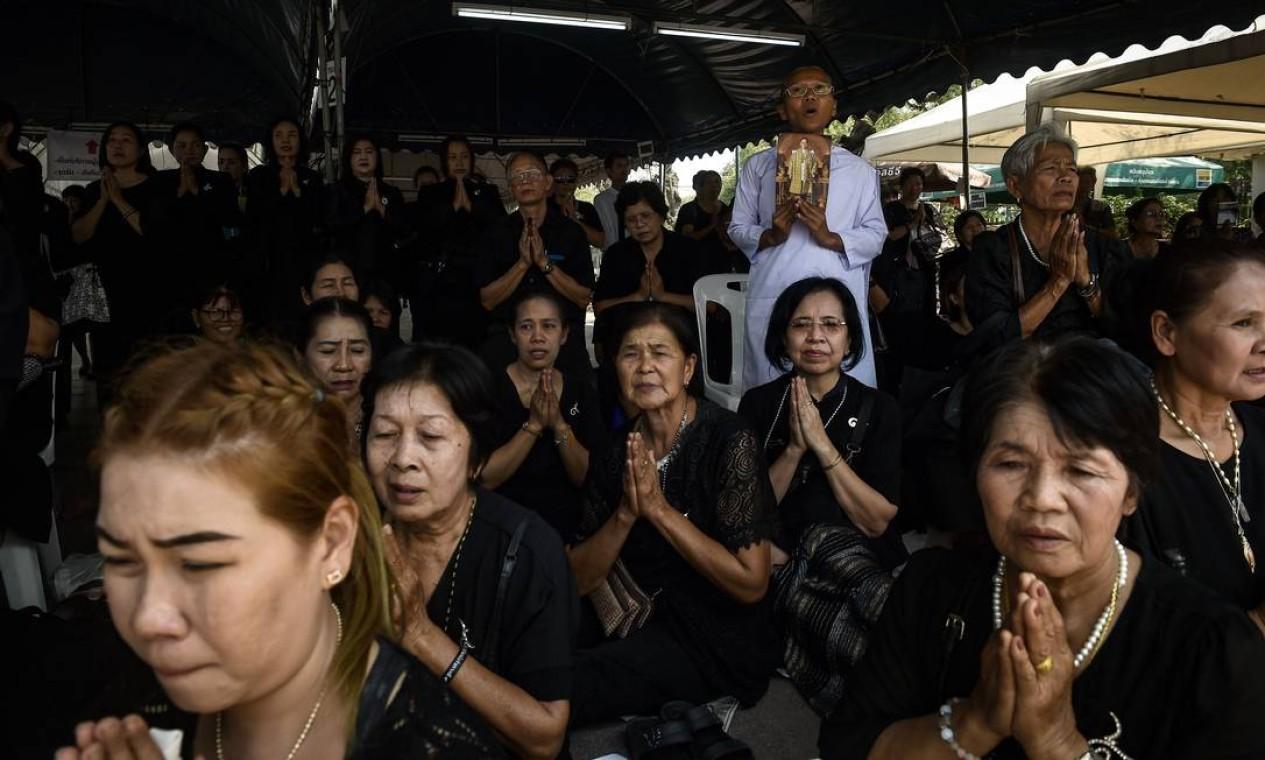 Em Bangcoc, tailandeses vestidos de preto prestam homenagem ao rei morto Foto: LILLIAN SUWANRUMPHA / AFP