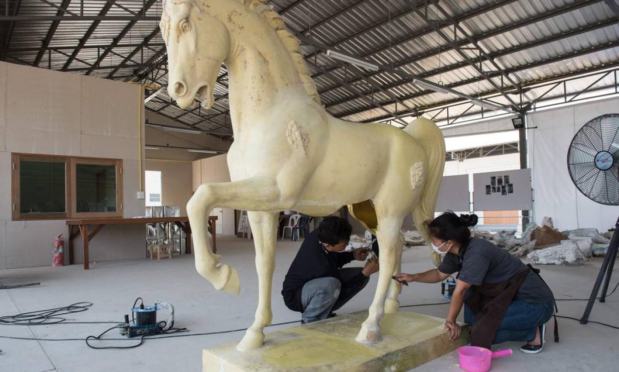 Desenhos e esculturas são preparados para a despedida final de Bhumibol. Seu corpo será cremado somente no fim deste ano Foto: ROBERTO SCHMIDT / AFP