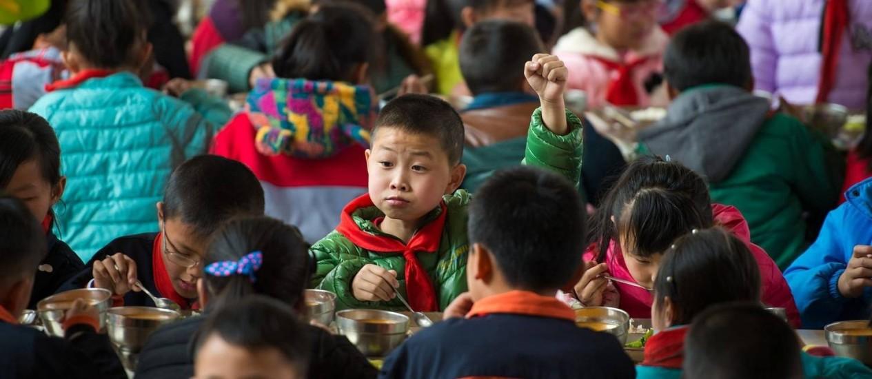 Crianças almoçam em escola na província de Hubei: custos com a criação dos filhos impede o aumento das famílias, mas o governo precisa reverter a curva de natalidade Foto: AFP