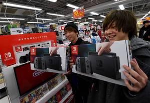Hiroki Higuchi e Tomohiro Yagi mostram os aparelhos Switch comprados no lançamento em Tóquio Foto: TOSHIFUMI KITAMURA / AFP