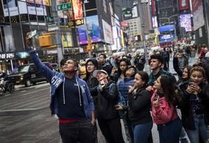 Turistas posam para foto na Times Square, em Nova York. Segundo pesquisa, a procura de viagens para os EUA diminuiu desde o veto migratório assinado por Trump Foto: Drew Angerer / AFP