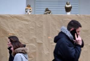 Pedestre fala ao celular enquanto caminha em frente a manequins de loja em Londres Foto: BEN STANSALL / AFP