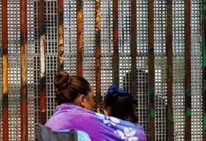 No México, mulher com filho no colo conversa com o marido, que está do outro lado da fronteira nos EUA Foto: JORGE DUENES / REUTERS