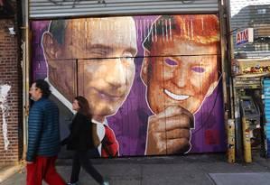 Pedestres caminham em frente a grafite do presidente russo, Vladimir Putin, segurando uma mascara de Trump, em Nova York Foto: SPENCER PLATT / AFP