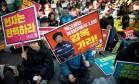 Críticos de Park exibem cartazes do lado de fora da Corte Constitucional Foto: KIM HONG-JI / REUTERS