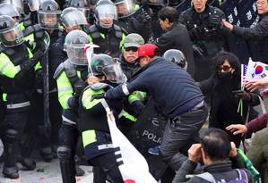 Apoio a Park. Partidários da presidente deposta, Park Geun-hye, enfrentam policiais na frente do Tribunal Constitucional, em Seul. Duas pessoas morreram nos confrontos Foto: JUNG YEON-JE/AFP