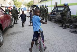 Menino anda de bicicleta em meio a soldados brasileiros em Porto Príncipe Foto: Dieu Nalio Chery / AP