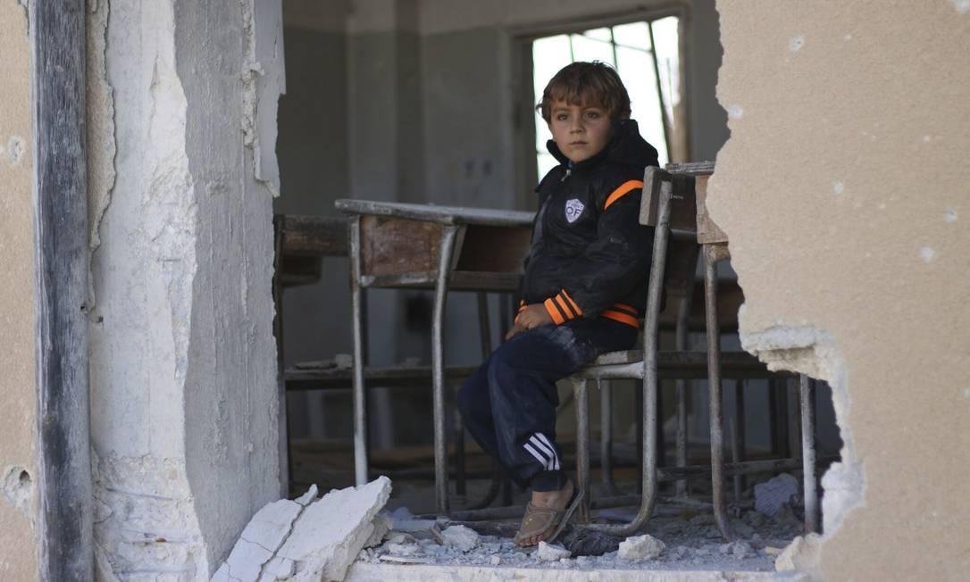 O garoto sírio Ahmed, de 6 anos, se senta em uma escola destruída, em Idlib, no norte da Síria Foto: Uncredited / AP