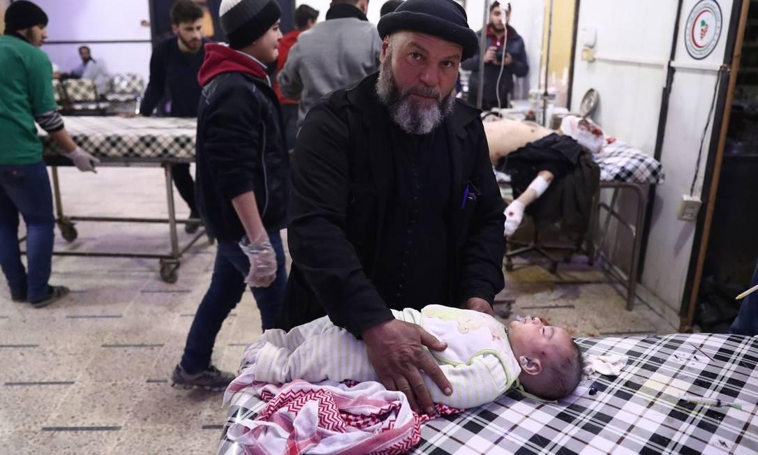 Homem cuida de bebê que sofreu ferimentos em ataque aéreo em Douma; segundo Unicef, 2016 foi o ano mais mortal para as crianças na Síria desde o início da guerra Foto: ABD DOUMANY / AFP