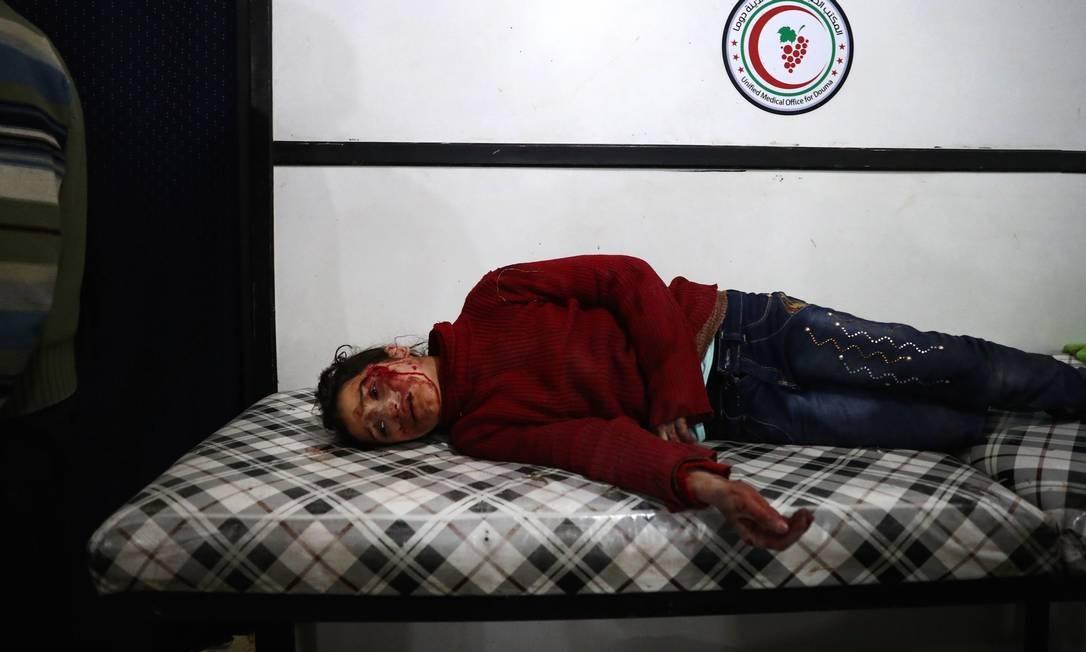 Menina com graves ferimentos no rosto e visivelmente abalada aguarda atendimento médico na Síria; pelo menos 255 crianças foram assassinadas dentro ou perto de uma escola em 2016 Foto: ABD DOUMANY / AFP