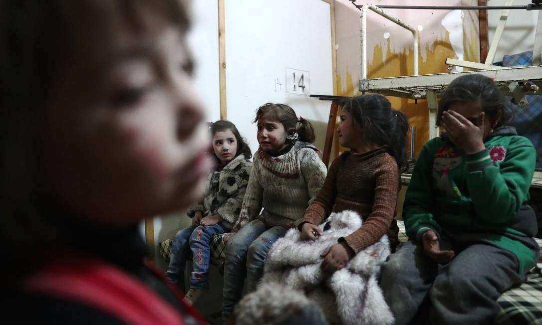 Meninas choram após serem atingidas por ataque aéreo do regime de Bashar al-Assad; relatório do Unicef diz que, no ano passado, não houve diminuição de ataques a escolas, hospitais, parques e casas Foto: ABD DOUMANY / AFP