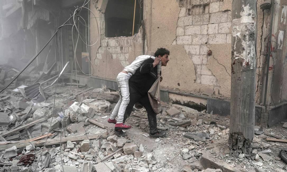 Homem carrega criança ferida nos ombros, enquanto foge dos escombros deixados por bombardeio perto de Damasco Foto: SAMEER AL-DOUMY / AFP