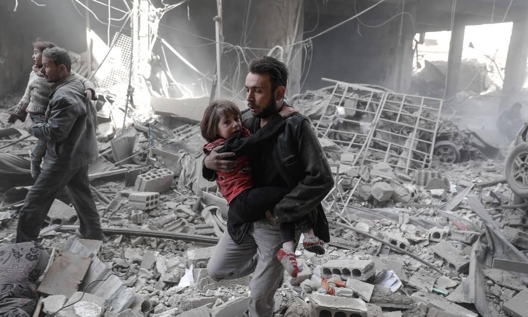 Homens carregam crianças pequenas após ataque aéreo em Douma; segundo a ONG Save The Children, a Síria vive uma crise de saúde mental infantil, uma vez que muitas crianças ficam traumatizadas pela violência da guerra Foto: SAMEER AL-DOUMY / AFP