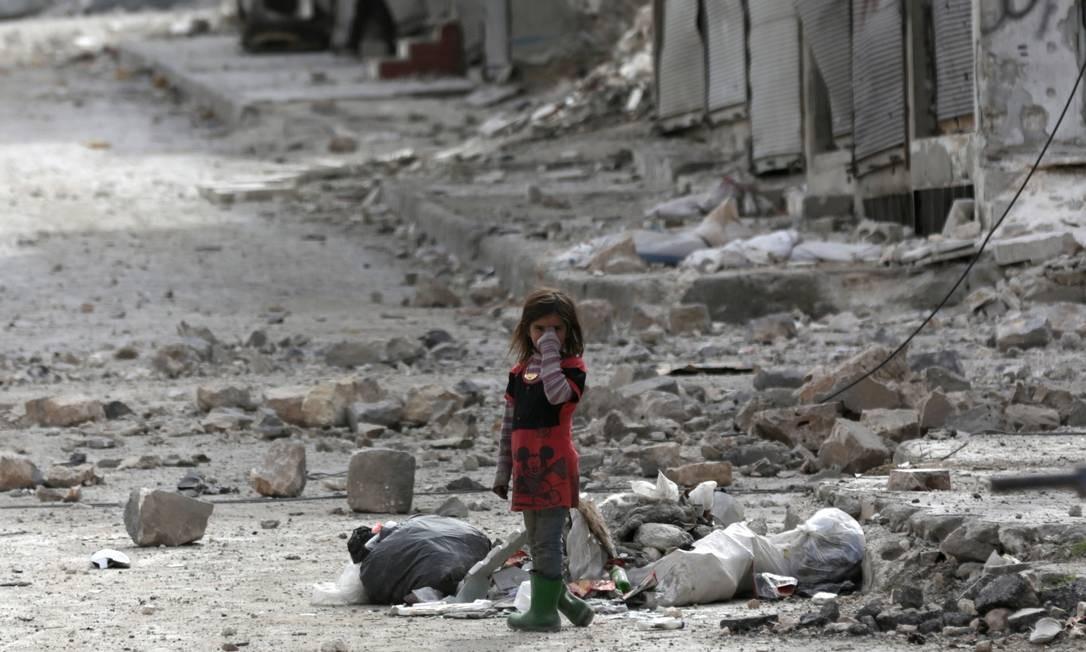 Sozinha, menina anda pelas ruas da cidade de al-Bab, na Síria, cujos prédios ficaram destruídos pela guerra civil; confrontos já duram seis anos Foto: KHALIL ASHAWI / REUTERS