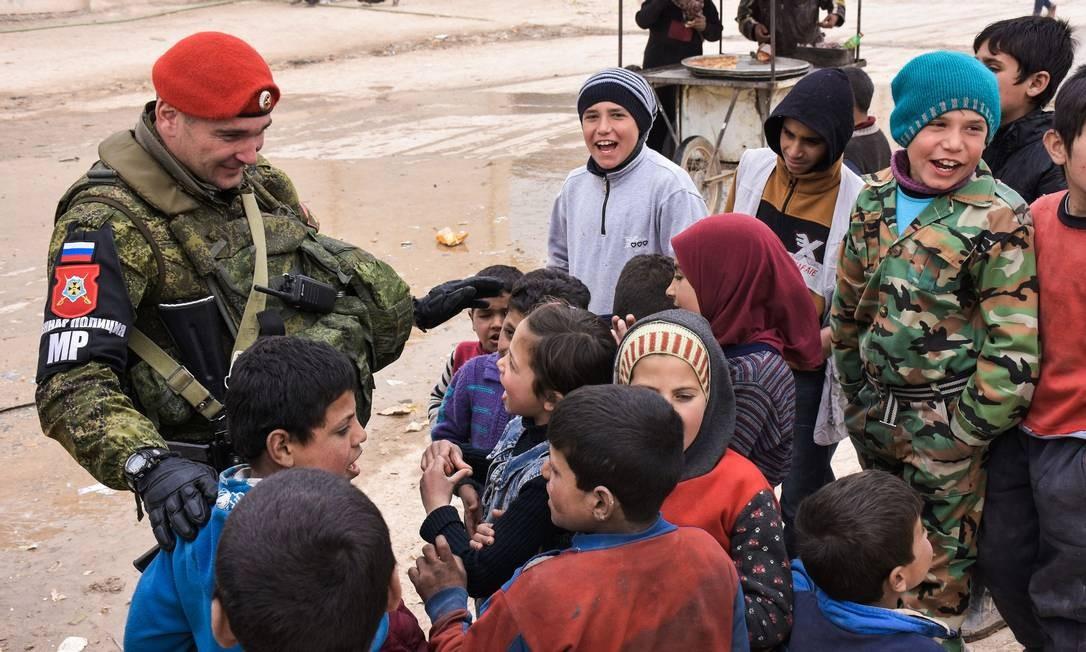 Militar russo conversa com crianças sírias deslocadas, enquanto Exército de Moscou distribuía vacinas e ajuda médica para hospitais pediátricos em abrigos de Jibreen, perto de Aleppo Foto: GEORGE OURFALIAN / AFP