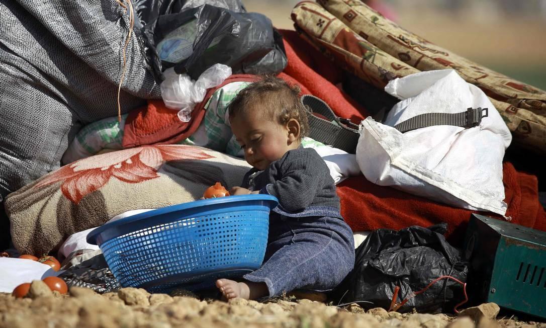 Bebê senta no chão de campo para deslocados perto da cidade de Mabij; famílias de Aleppo, cidade devastada pela guerra, se dirigem para lá em busca de segurança Foto: DELIL SOULEIMAN / AFP