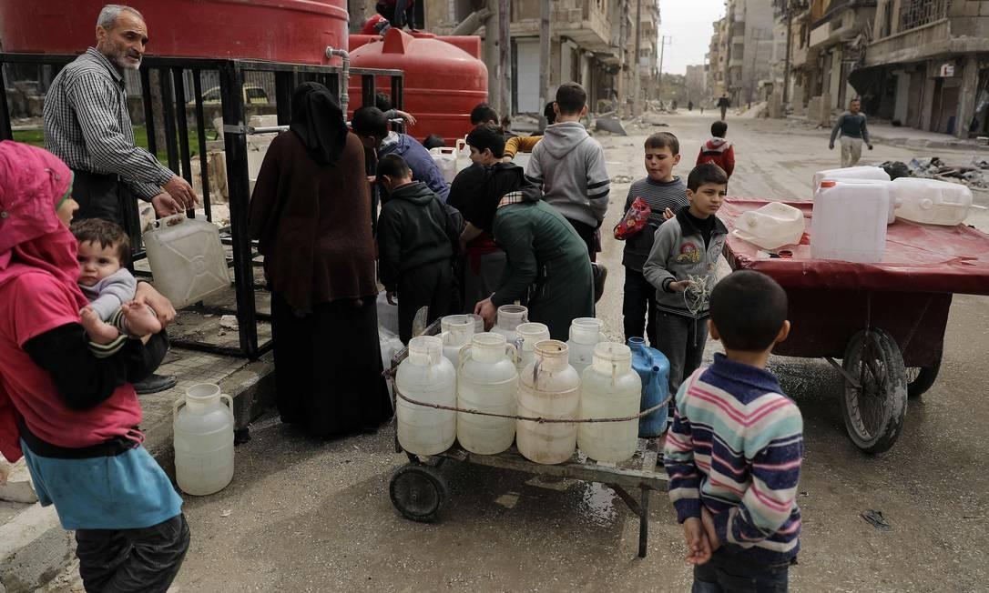 Crianças sírias formam fila em reservatório de água no bairro de Shaar, em Aleppo, que já foi controlado por rebeldes Foto: JOSEPH EID / AFP