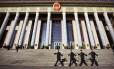 O Grande Salão do Povo é um suntuoso monumento na Praça da Paz Celestial, local histórico de Pequim; agentes de segurança caminham em frente ao edifício parlamentar, em dia de forte operação policial para proteger milhares de autoridades que se reuniram ali