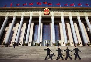 O Grande Salão do Povo é um suntuoso monumento na Praça da Paz Celestial, local histórico de Pequim; agentes de segurança caminham em frente ao edifício parlamentar, em dia de forte operação policial para proteger milhares de autoridades que se reuniram ali Foto: Mark Schiefelbein / AP