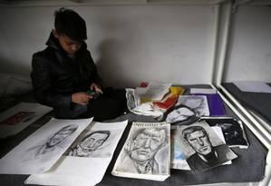 Farhad Nouri senta na sua cama ao lado de desenhos que ele mesmo fez em Belgrado, na Sérvia Foto: Darko Vojinovic / AP