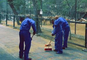 Em imagem divulgada pelo governo de Dubai, os três condenados são vistos varrendo a calçada Foto: Uncredited / AP