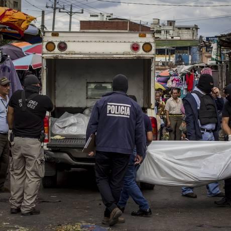 Policiais carregam o corpo de um vítima depois de troca de tiros entre gangsteres e seguranças privados, em um mercado central, em San Salvador, capital Foto: Salvador Melendez / AP