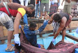 Pescadores iemenitas carregam o corpo de um refugiado somali, morto em ataque por um helicóptero enquanto viajava em um barco ao largo da costa do Iêmen Foto: ABDULJABBAR ZEYAD / REUTERS