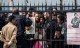 Em março de 2016, imigrantes esperam atrás de grades após terem sido pegos tentando passar da Turquia para a Grécia