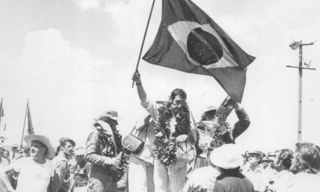 GP Brasil. No pódio, o campeão José Carlos Pace ergue uma bandeira do Brasil entre Emerson Fittipaldi, segundo colocado, e Jochen Mass, terceiro Foto: Antonio Carlos Piccino 26/01/1975 / Agência O Globo