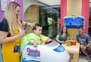 Diversão. Acompanhados dos pais, Regina e Nélio Trindade, Théo faz seu novo corte de cabelo na cadeira-avião
