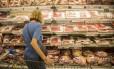 Consumidor observa carnes em supermercado