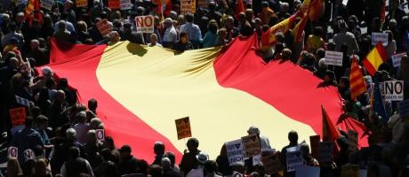 Manifestantes seguram cartazes e uma enorme bandeira da Espanha, atendendo ao chamado da Sociedade Civil Catalã (SCC) para ir às ruas contra a separação da Catalunha Foto: PAU BARRENA / AFP