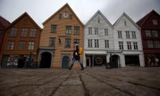 Mulher anda perto de zona portuária na cidade de Bergen, Noruega Foto: STOYAN NENOV / REUTERS