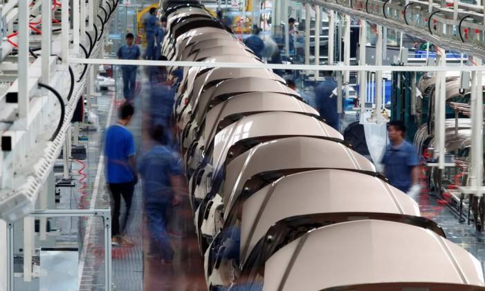 Homens trabalham em linha de produção de automóveis na província de Zhejiang, na China Foto: © Carlos Barria / Reuters / REUTERS
