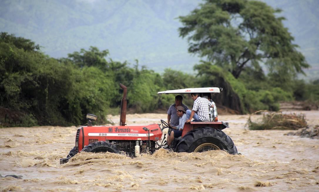 Peruanos que vivem no campo usam trator para atravessar correnteza provocada por chuvas; 72 pessoas morreram em decorrência do desastre natural JULIO REANO / AFP