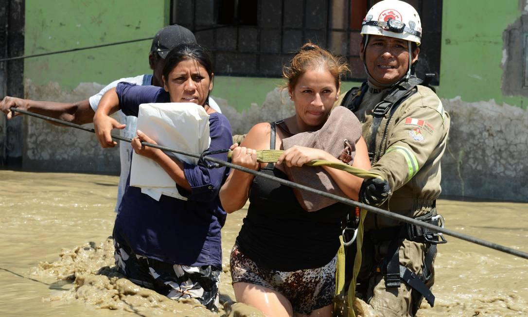 Socorristas ajudam moradores a deixar suas casas na cidade de Huarmey; várias localidades sofrem com falta de água após as linhas de fornecimento terem sido comprometidas CRIS BOURONCLE / AFP