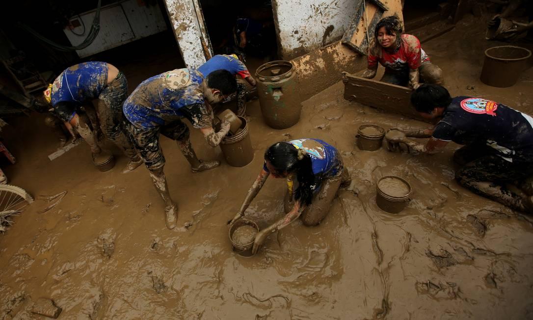 Voluntários limpam casa coberta de lama após ser atingida por enchentes de rios em Cajamarquilla; 70 mil pessoas já ficaram desabrigadas no país MARIANA BAZO / REUTERS