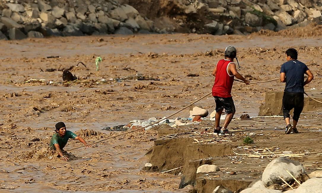 Homens usam corda para atravessar rio em Huachipa; previsão é que Peru aindaenfrente mais um mês de fortes chuvas MARIANA BAZO / REUTERS