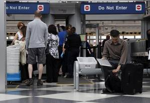 Passageiros passam por verificação de segurança em aeroporto de Chicago Foto: Kiichiro Sato / Associated Press